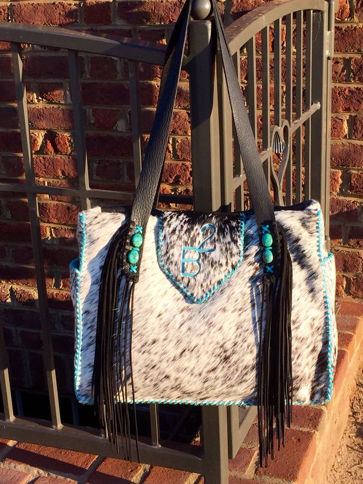 The Buckaroo Diaper Tote. Cowhide, turquoise stones, hand cut suede fringe, and the customers brand in turquoise suede.  gowestdesigns.us