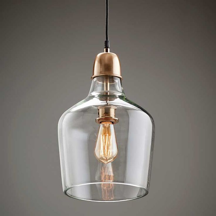 these two copper see through edison bulb pendants hang over the butcher block island - Glass Pendant Lighting