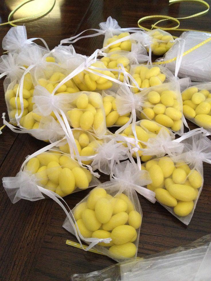 Saquinho de organzas branco com amêndoas confeitadas amarelas.