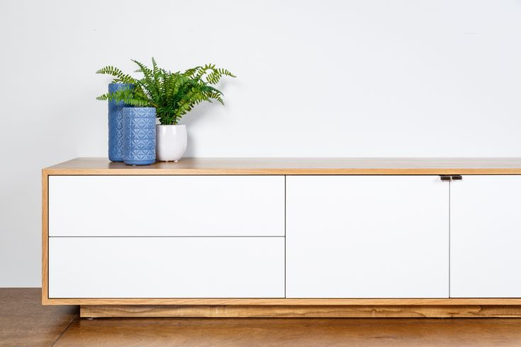 Tribeca Lowline TV Unit. Pictured in WA Marri Veneer with Monument grey doors and drawers. Features our new side mount doors for a space saving and push to open drawers.