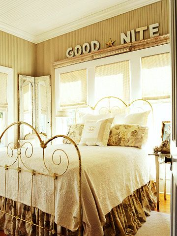 Feminine curves on the rustic iron bed frame suit the romantic nature of cottage decorating. Look for antique pieces of furniture at garage sales or thrift stores to get the look for less.