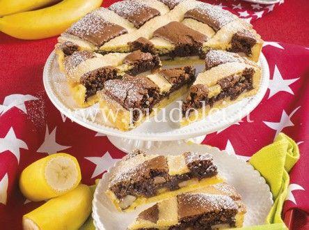crostata-ciocco-bananaIngredienti frolla: 330 g di farina 150 g di zucchero a velo 170 g di burro 1 uovo 1 tuorlo 1 pizzico di sale 1 pizzico di vanillina farcia: 100 g di farina di mandorle 2 uova 100 g di zucchero 50 g di burro 10 g di cacao 100 g di cioccolato fondente 250 g di banane tagliate a rondelle 1 cucchiaino raso di lievito decorazione: zucchero a velo Preparazione 1 2 3 4 5 6 Frolla: impastate velocemente tutti gli ingredienti. Formate un panetto, appiattitelo e, protetto con…