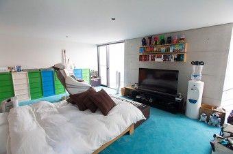 ベッドルームのカーペットの色はブルー。カラフルなキャビネットの先には、大型のウォークインクローゼット。