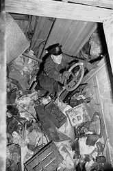 A policeman searching the New York home of the Collyer brothers, perhaps history's most famous hoarders