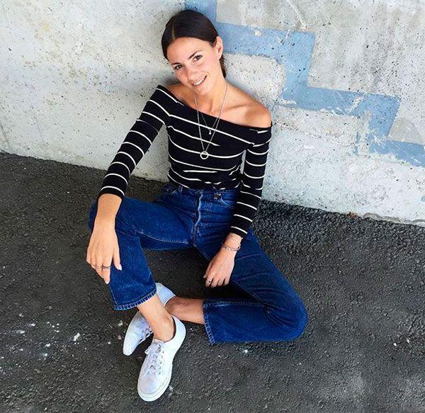 Look street style de blusa com ombros de fora listrada + calça jeans.