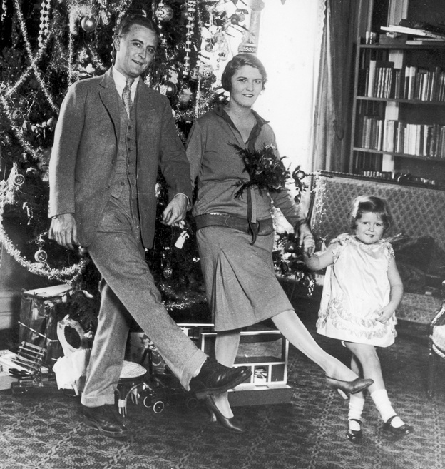 """F. Scott Fitzgerald dances with his wife, Zelda, and daughter, Frances """"Scottie,"""" in front of a Christmas tree in Paris."""