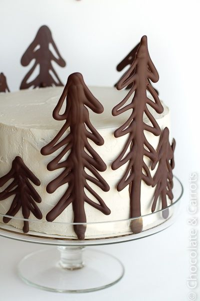 Draw Christmas trees on parchment paper using melted chocolate. Place in refrigerator to harden then remove and place around cake.