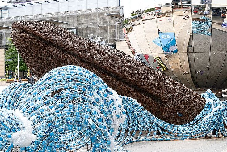 """""""The Bristol Whales,"""" is a life-size environmental art installation in Bristol, UK, constructed by Cod Steaks, a design & model-making firm. It depicts two of the massive mammals emerging out of an """"ocean"""" of plastic. The whales are woven from biodegradable willow. The waves of water are constructed from 70,000 plastic water bottles discarded by spectators and runners at two races. At night the installation is illuminated with LED lighting. 