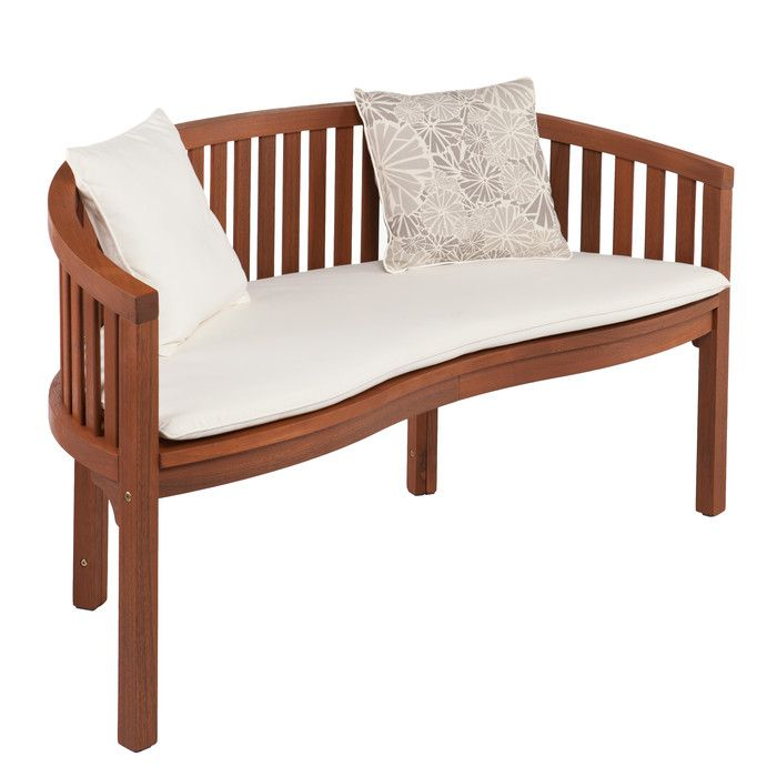 Round out your patio scene with this contemporary, banana-style outdoor bench. Quick drying slats, exposed hardwood, a soft white cushion and pillows hint at craftsmen inspiration. Share a seat with friends or relax solo on an outdoor bench that excites the senses. This bench is made of sustainable Brazilian eucalyptus hardwood produced on FSC certified production lines. Cushion fabric features special UV inhibitors for long lasting color. Slight variations in natural hardwood may occur.