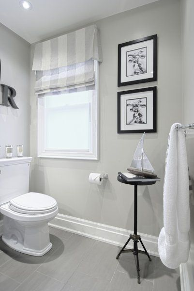 Grey paint, white baseboard, striped roman shade, black accent. Perfect simple bathroom.