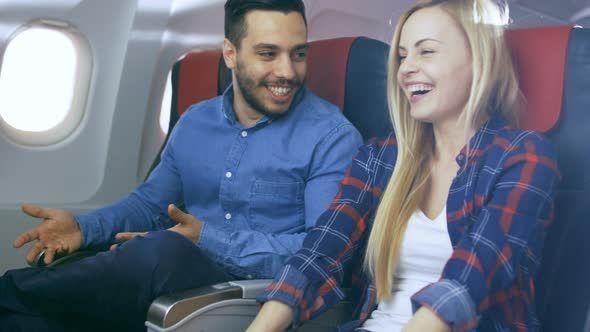 Plane Flight Handsome Hispanic Man Tells Funny Story to His Beautiful Blonde Girlfriend. Both Laugh.