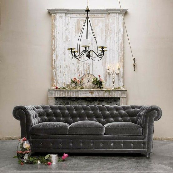 This distressed fireplace mantel and tufted sofa are epic