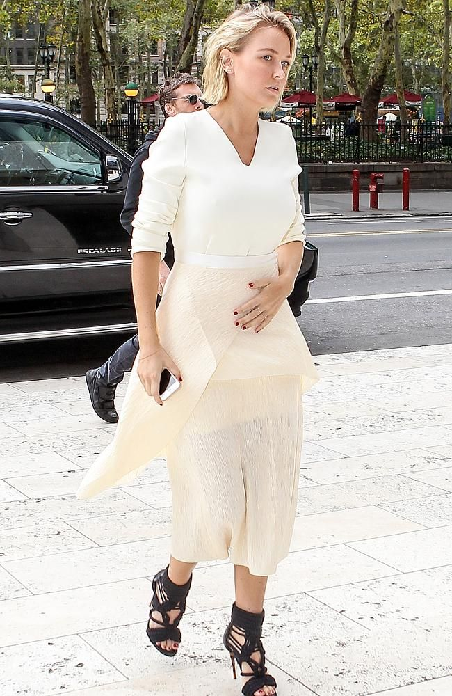 Lara Bingle placed her hand over her stomach as she entered the building.
