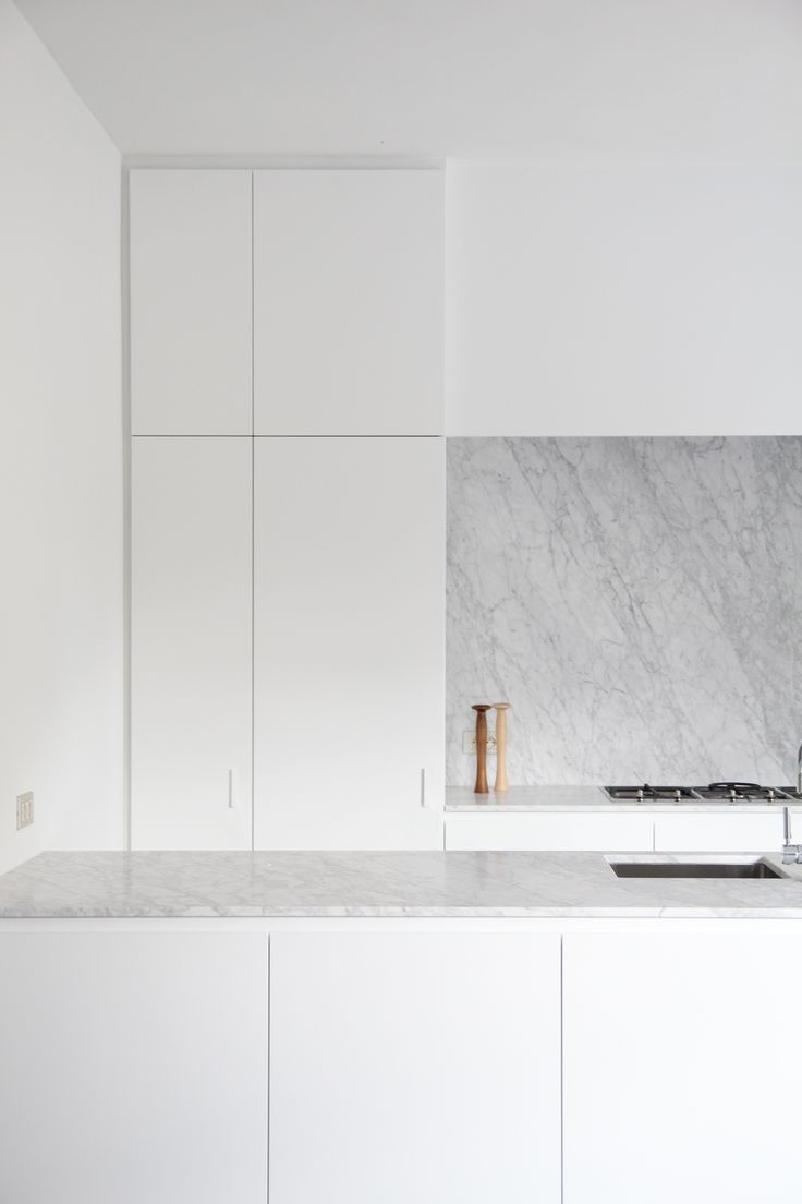 Nice and sleek plus it includes lots of cupboards, solid slab as a backsplash is nice Kitchen - by Rolies + Dubois architecten