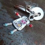 Porte-clé capsule bonhomme mosaïque multicolore. Composition : capsule de canette, pâte polymère, perles, écrou. Prix : 10 euros
