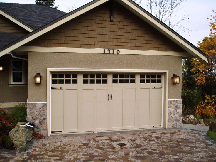 The simple panel design of this Clopay Coachman Collection carriage house garage door blends perfectly with the clean lines of this Craftsman style home. The door color is the perfect complement to the warm brown tones found in the stone on the facade and the paver driveway. Model shown: Design 12 with SQ24 windows and decorative Spade Strap Hinges and Lift Handles. Installed by Harbour Door Services, Victoria, B.C.