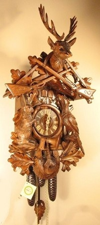 Model #8396 Huge Live Animal Hunters Cuckoo Clock     This hunting cuckoo clock is an example of the finest carving available. Its traditional carved scene depicts the day of the hunt. A majestic deer head stands above with guns hanging below, carved with intricate detail. On the body of the clock the careful viewer can see the animals of the forest, surrounded by oak leaves, a hunting horn, and an ammunition pouch.