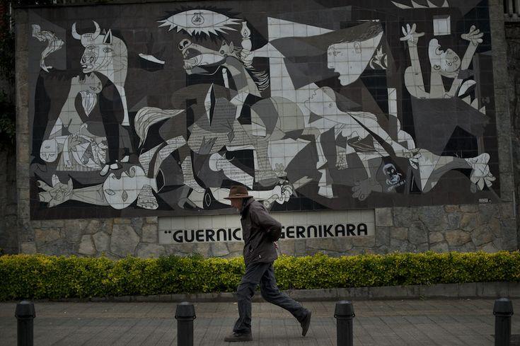 """IlPost - Guernica, Spagna - Un uomo passeggia davanti a un muro con una riproduzione del dipinto di Pablo Picasso """"Guernica"""", nell'omonima città spagnola. Sabato 26 aprile è stato il 77esimo anniversario del bombardamento aereo a tappeto su Guernica, uno dei più duri della guerra civile spagnola (AP Photo/Alvaro Barrientos)"""