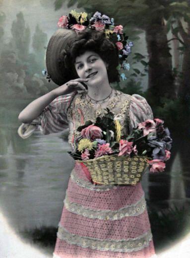 Фото цветочницы в ретро стиле. Букетами наполнена большая корзина, цветочная гирлянда украшает широкие поля шляпы.