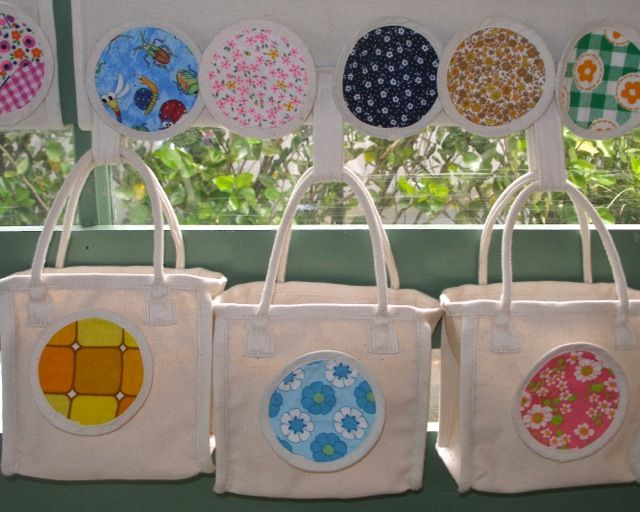 children's small carry bags with fabric circles, hanging on a velcro panel