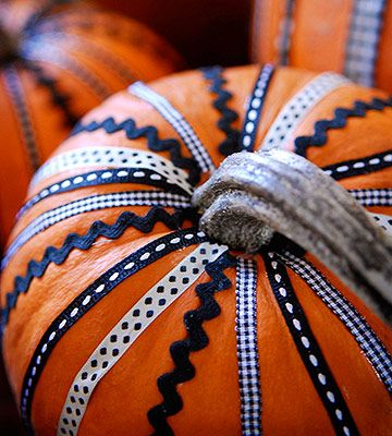 Use a mix of different ribbon and rickrack to decorate your pumpkin. For a quick and easy method, start at the top of the pumpkin near the stem, and hot-glue the trim along the veins of the pumpkin.
