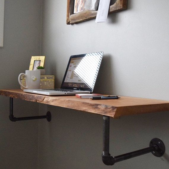 Perfect for stylish space-savers, this minimalist, wall-mounted live edge desk is finished from rough sawn reclaimed hardwoods (walnut, cherry, maple and others) harvested from the Detroit metro area; the desk is mounted to the wall using both a French cleat as well as side-braced metal piping to add a modern industrial look and provide additional stability. Wood is oiled and finished with an acrylic coating to provide protection against normal wear. Order includes instructions and hardware…
