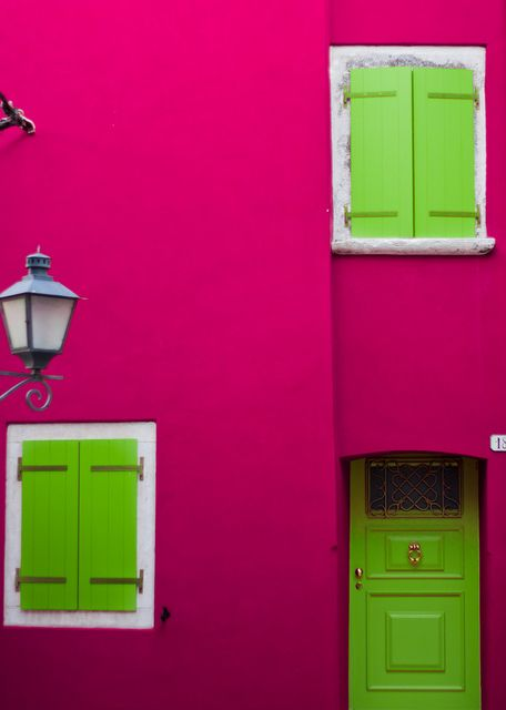 Rovinj, Croatia. Bright pink wall and lime green door and shutters.