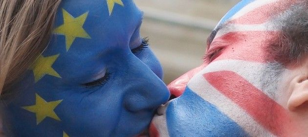 TOPSHOT - A couple with their faces painted in the flags of the European Union and Great Britain kiss in front of the Brandenburg Gate in Berlin on June 19, 2016. The action, which took place in several cities in Europe, aims to encourage the people in Great Britain to vote in favour of remaining in the EU in next week`s referendum.