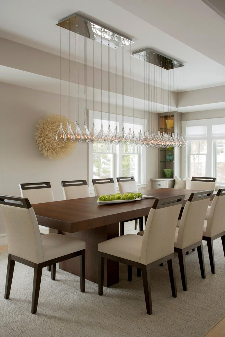 This modern dining room space features a long glass chandelier hung over a warm wood dining table adding a touch of elegance to the stark, modern space.