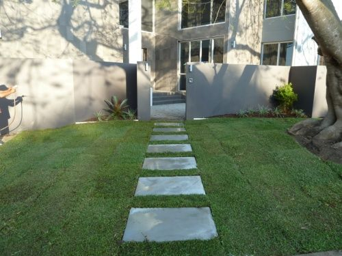 1200 * 600 concrete pads layed on a concrete base create an informal stylish entry to house. It is then softened with turf.