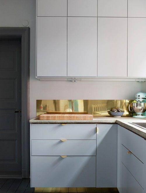En glänsande & effektfull detalj i ett kök kan vara att ha mässingsdetaljer i köket. I detta kök har de mässing både som golvsocklar & stänkskydd, men även som låd- & dörrhandtag & som vattenblandare…