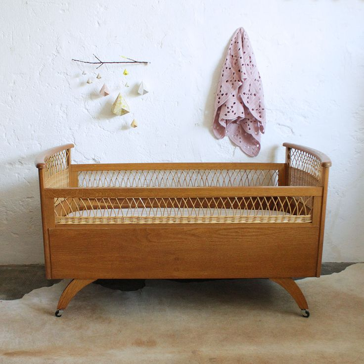 Adorable lit bébé en bois et rotin des années 50. De la naissance à 2-3 ans. Très beau travail du rotin avec ses motifs croisillons. La tête et le pied de lit sont délicatement incurvés. Sur roulettes pour un déplacement simplifié. Entièrement démontable, facilitant le rangement. Sommier bois d'origine. Matelas standard non fourni (120 x 60 cm), nous consulter. Ce lit sera soigneusement nettoyé à