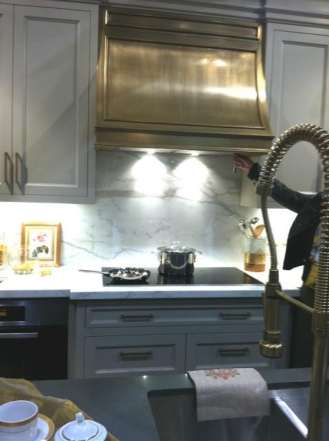 Brass hood, gray cabinetry
