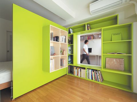 hidden plywood door with built-in bookshelves that forms a reading nook. so clever!
