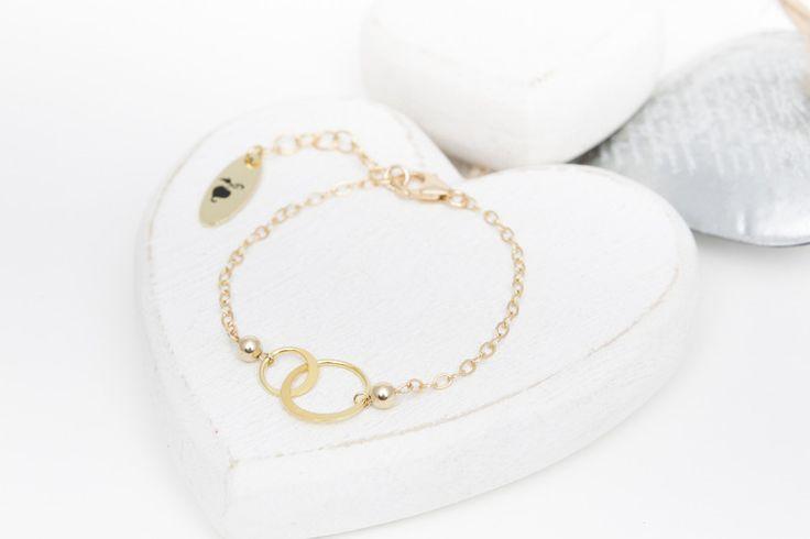 Die 2 verschlungende Ringe, verziert mit kleinen Perlen, sind der Hingucker dieser zierlichen hochwertig vergoldeten Infinity / Karma Armbänder. Das **Set beinhaltet 2 Armbänder und eine hübsche...