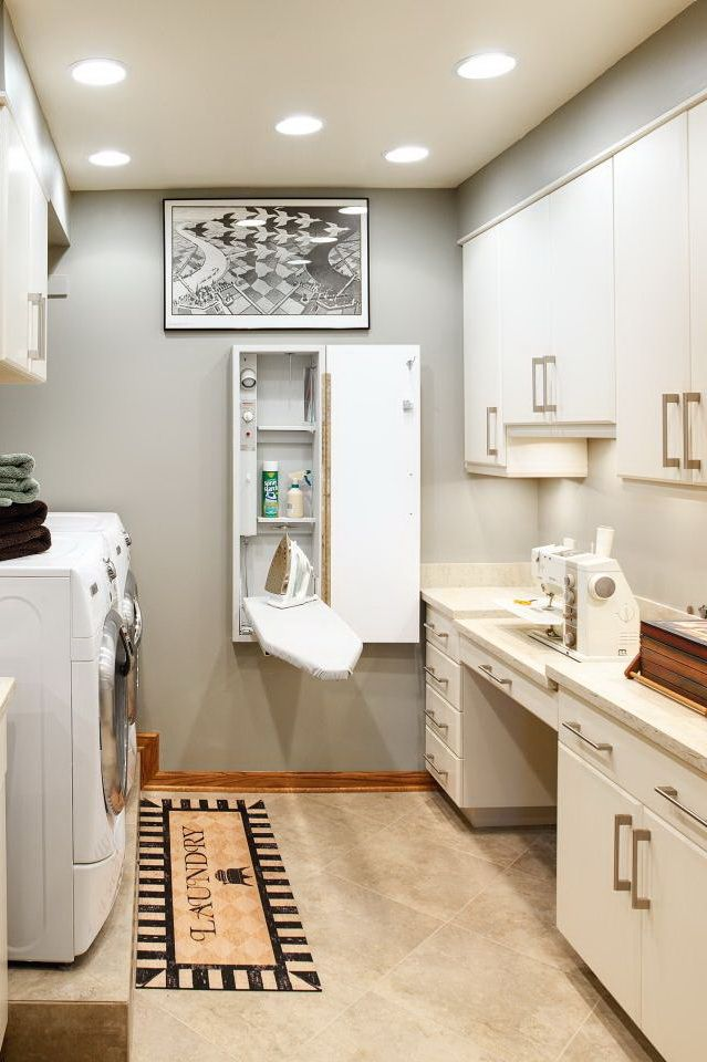 Utility is the name of the game in this neutral laundry room. A stainless steel utility sink, sewing machine nook and a murphy-style ironing board create separate stations around the room, while white cabinetry offers storage throughout.