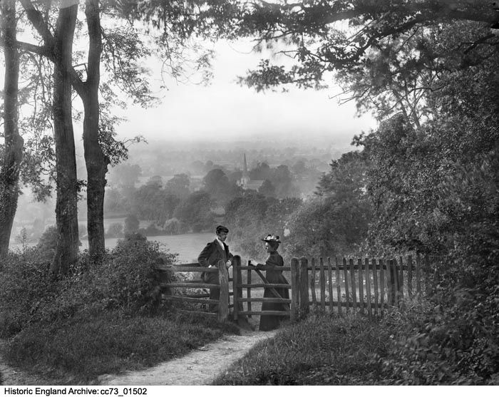 CC73/01502 A couple posing by a gate with the spire of the Saxon church and surrounding countryside in the background. St Lawrences Church, Mickleton, Gloucestershire.  Date:1860 - 1922 Photographer: Henry W Taunt