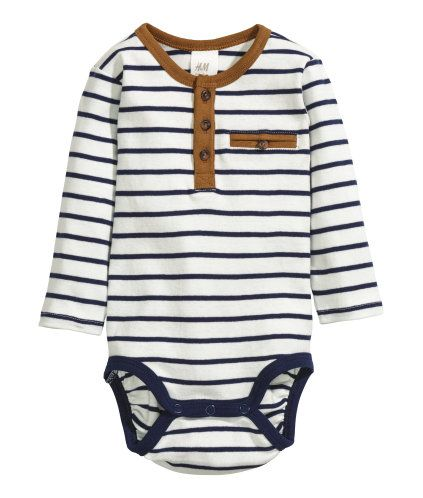 White. Long-sleeved bodysuit in soft, striped cotton jersey. Buttons at front, small chest pocket, and snap fasteners at gusset.