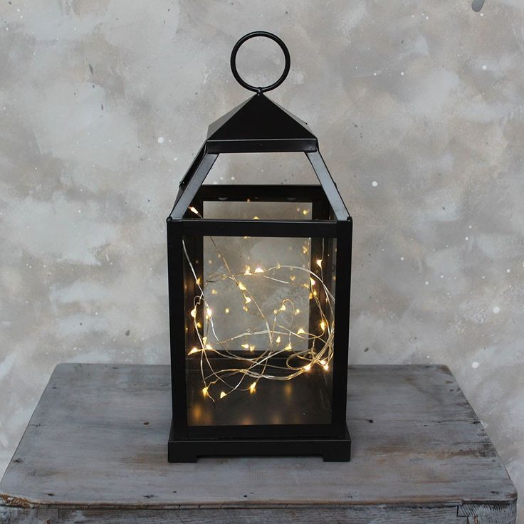 """Black metal candle lantern with glass sides. Use for wedding decor, home table tops, and ambient lighting. A simple yet chic wedding decoration for an evening reception. - 5.25"""" Wide x 12"""" Tall Shop A"""