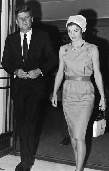 The President and Mrs. Kennedy in Palm Beach, Florida. Jackie in a beige shift dress with button detail & trademark accessories. (1961)