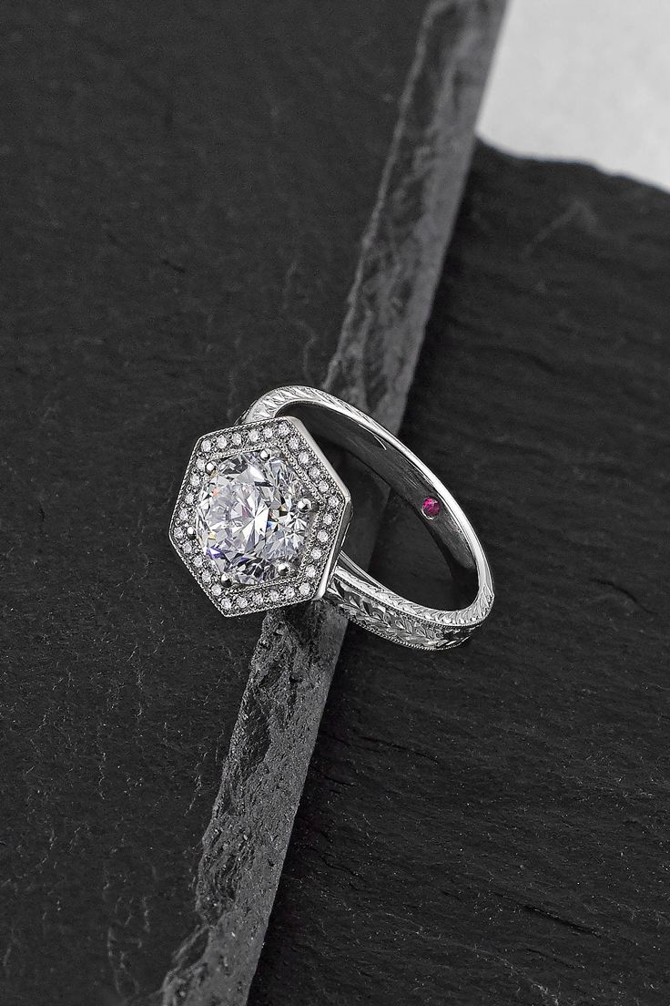 A Taylor & Hart engagement ring fit for a queen! Create your very own with our help! Draw inspiration from this round diamond with hexagonal diamond halo finished with milgrain and hand-engraved band set in platinum.