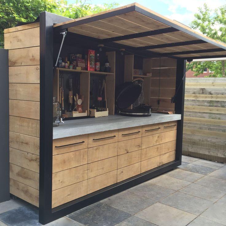 Kleine zomerkeuken gemaakt van hout en zwart metaal, die kan worden gesloten in geval van