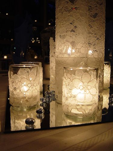 Candle centerpieces that were made simply by wrapping lace around various sized votive candles. Placed atop a mirror to reflect light and surrounded by small details like these decorative rocks, this make a stunning centerpiece.