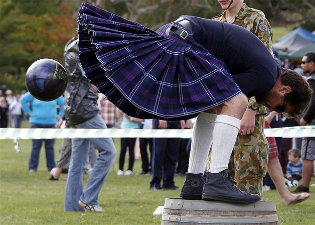Brigadoon-Always in April: A competitor wearing a kilt & standing on a barrel throws a ball between his legs during the 'brigaball' contest at the 36th Bundanoon Highland Gathering, in the Southern Highlands of New South Wales, Australia, on April 6 (© David Gray/Reuters)