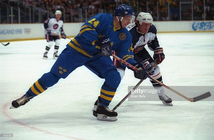Jeremy Roenick of the USA defends as Patric Kjellberg of Sweden goes after the puck at Big Hat Arena during the 1998 Winter Olympic Games in Nagano, Japan. Mandatory Credit: Brian Bahr /Allsport