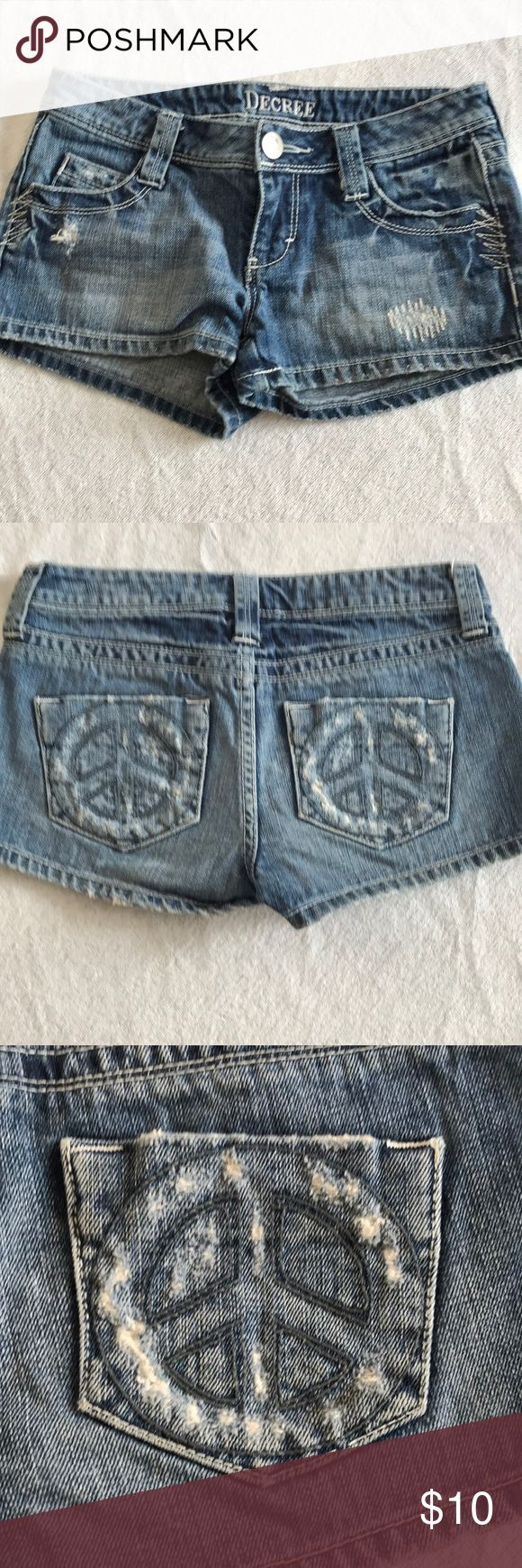 """Decree Distressed denim shorts size 0 Slightly distressed denim shorts, size 0. Slight fraying around the bottoms. Cute peace sign design on back pockets. Button and zip fly.  Waist measures 14"""" flat across, 6"""" rise and 2"""" inseam any questions please ask Decree Shorts Jean Shorts"""