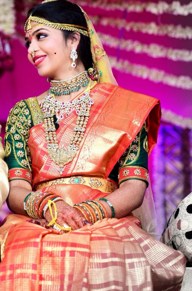 South Indian bride. Temple jewelry. Jhumkis.Red pink silk kanchipuram sari with contrast green blouse.Braid with fresh jasmine flowers. Tamil bride. Telugu bride. Kannada bride. Hindu bride. Malayalee bride.Kerala bride.South Indian wedding.