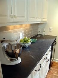 White cabinets, black counter tops, and tan back splash
