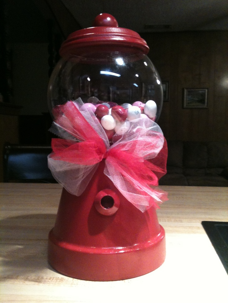Gumball machine I made for my daughters teachers.  You need a six inch terra cotta pot, a 4 inch terra cotta saucer, a clear round glass globe (I got it at Wal-Mart for 1.97 in craft department), 1 can spray paint your color choice, ribbon color of your choice, doll pin stands and round wood balls from Hobby Lobby unfinished wood section, and E6000 glue.  Spray  the pot, saucer, and wood pieces.  Then glue the globe to pot, wooden ball to saucer and doll pin stand to pot.  Let dry 24 hrs.