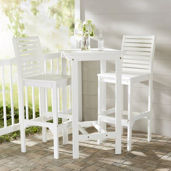 Enjoy the outdoors in style with this lovely bar set, showcasing slatted chairs and a classic white finish. Top it with a glass vase filled with seashells and starfish-embroidered placemats for a pop of beach-chic style in your backyard.